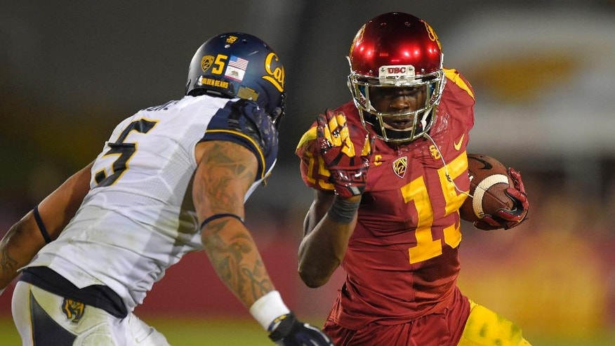 Southern California wide receiver Nelson Agholor, right, fends off California safety Michael Lowe during the first half of an NCAA college football game, Thursday, Nov. 13, 2014, in Los Angeles. (AP Photo/Mark J. Terrill)