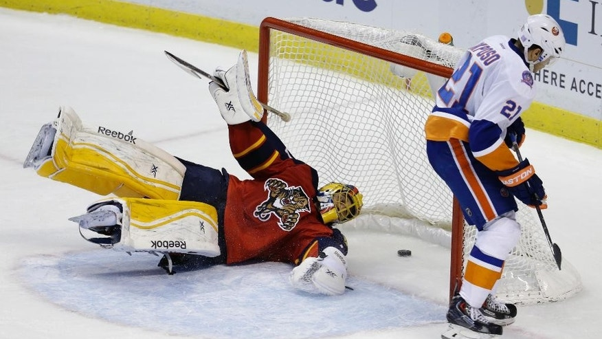 Florida Panthers goalie Roberto Luongo, left, falls to the ice after New York Islanders right wing Kyle Okposo (21) scored during a shootout in an NHL hockey game, Friday, Nov. 14, 2014, in Sunrise, Fla. The Islanders defeated the Panthers 4-3 in a shootout. (AP Photo/Lynne Sladky)