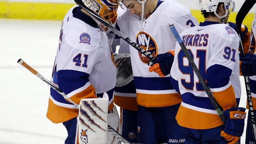 New York Islanders goalie Jaroslav Halak (41) is congratulated by teammate Travis Hamonic, center, after an NHL hockey game against the Florida Panthers, Friday, Nov. 14, 2014, in Sunrise, Fla. The Islanders defeated the Panthers 4-3 in a shootout. (AP Photo/Lynne Sladky)