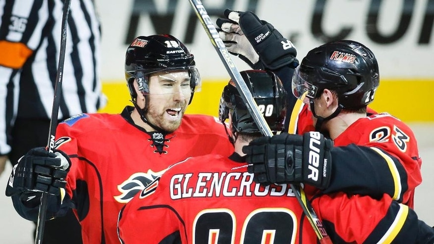 Calgary Flames' David Jones, left, celebrates his goal with teammates Curtis Glencross, center, and Sean Monahan during the third period of an NHL hockey game against the Arizona Coyotes in Calgary, Alberta, Thursday, Nov. 13, 2014. (AP Photo/The Canadian Press, Jeff McIntosh)