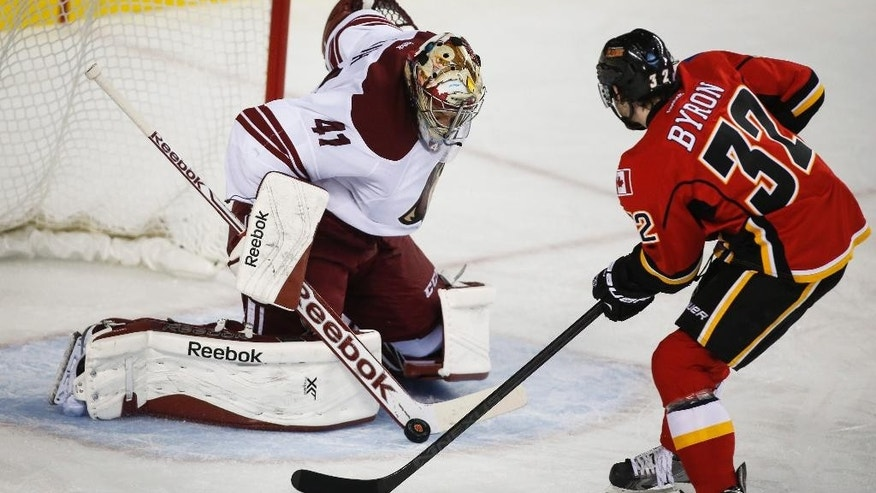 Arizona Coyotes goalie Mike Smith, left, stops a shot from Calgary Flames' Paul Byron during the third period of an NHL hockey game in Calgary, Alberta, Thursday, Nov. 13, 2014. (AP Photo/The Canadian Press, Jeff McIntosh)