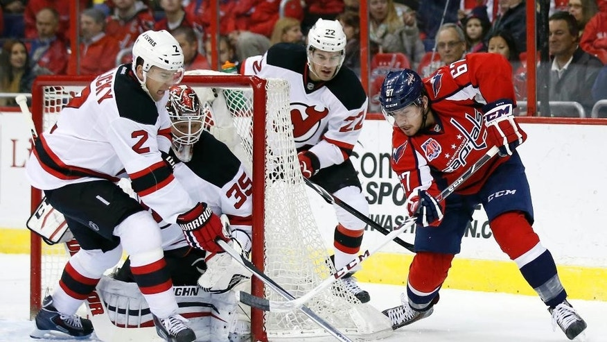 Washington Capitals center Chris Brown attempts to shoot as New Jersey Devils defenseman Marek Zidlicky (2), from the Czech Republic, goalie Cory Schneider (35) and defenseman Eric Gelinas (22) defend in the first period of an NHL hockey game, Friday, Nov. 14, 2014, in Washington. (AP Photo/Alex Brandon)