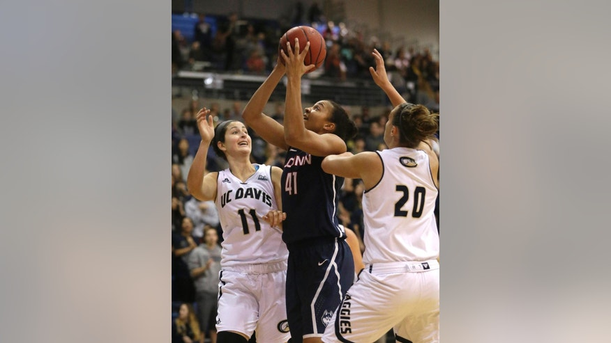 Connecticut center Kiah Stokes, center, goes to the basket between UC Davis' Lauren Beyer, left, and Celia Marfone, right, during the first half of an NCAA women's college basketball game in Davis, Calif., Friday, Nov. 14, 2014.(AP Photo/Rich Pedroncelli)