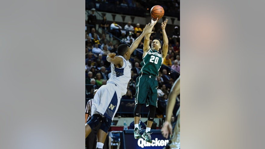 Michigan State's Travis Trice, right, shoots over Navy's Tilman Dunbar, left, during the first half of  an NCAA college basketball game Friday, Nov. 14, 2014, in Annapolis, Md.(AP Photo/Gail Burton)