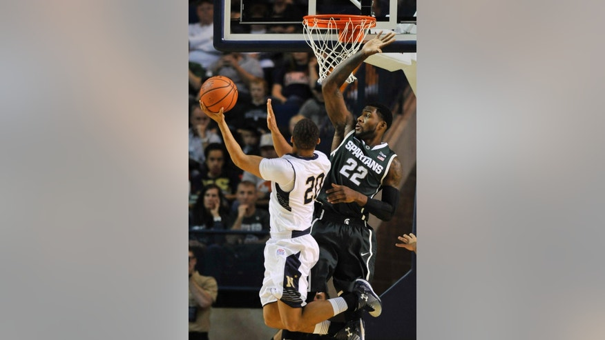 Michigan State's Branden Dawson, right, attempts to block a shot by Navy's Shawn Anderson during the first half of an NCAA college basketball game Friday, Nov. 14, 2014, in Annapolis, Md.(AP Photo/Gail Burton)
