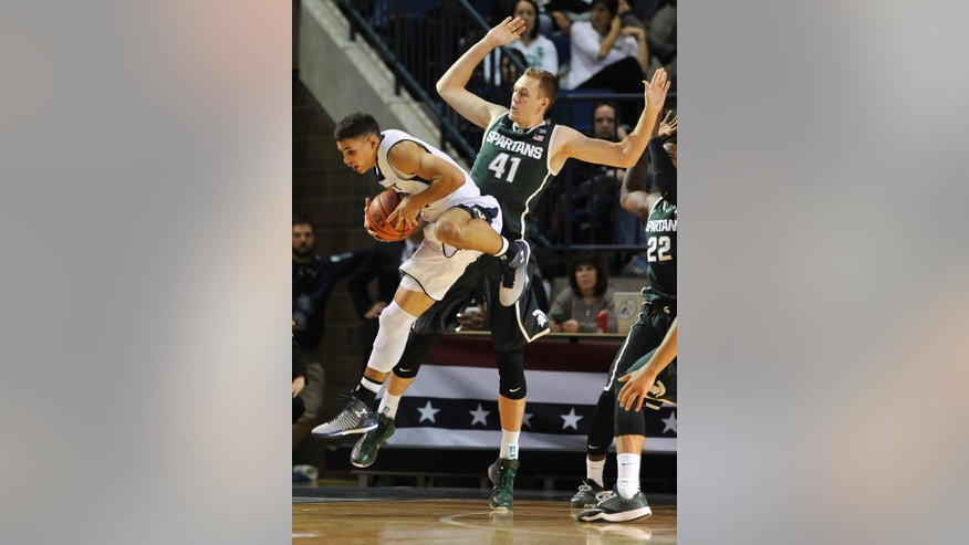 Michigan State's Colby Wollenman, right defends as Navy's Bryce Dulin jumps for a pass during the first half of  an NCAA college basketball game Friday, Nov. 14, 2014, in Annapolis, Md. (AP Photo/Gail Burton)