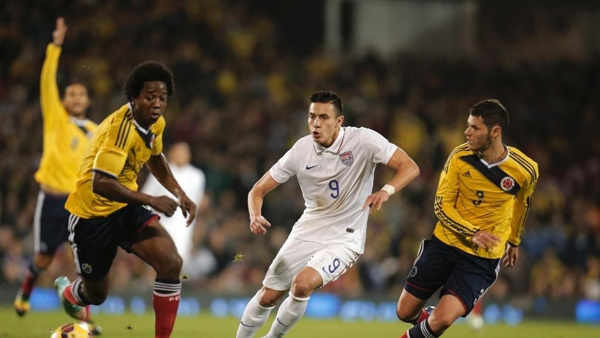 USA's Rubio Rubin, centre, passes the ball during an international friendly soccer match against Colombia at the Craven Cottage ground in London, Friday, Nov. 14, 2014. (AP Photo/Lefteris Pitarakis)