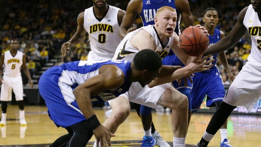 Iowa forward Aaron White, center, fights for a loose ball with Hampton guard Brian Darden, left, during the first half of an NCAA college basketball game, Friday, Nov. 14, 2014, in Iowa City, Iowa. (AP Photo/Charlie Neibergall)