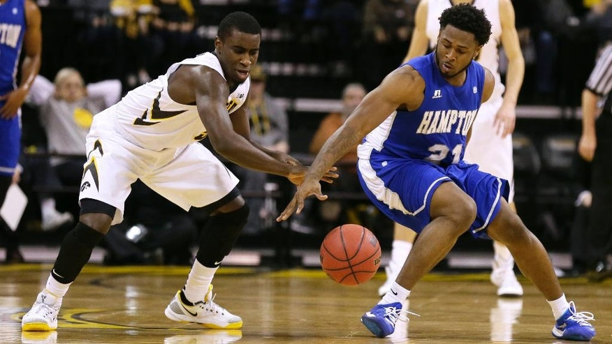 Iowa guard Anthony Clemmons, left, and Hampton guard Ke'Ron Brown reach for a loose ball during the first half of an NCAA college basketball game, Friday, Nov. 14, 2014, in Iowa City, Iowa. (AP Photo/Charlie Neibergall)