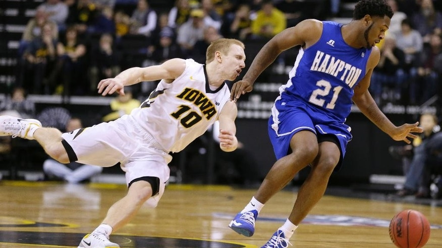 Iowa guard Mike Gesell, left, tries to steal the ball from Hampton guard Ke'Ron Brown, right, during the first half of an NCAA college basketball game, Friday, Nov. 14, 2014, in Iowa City, Iowa. (AP Photo/Charlie Neibergall)