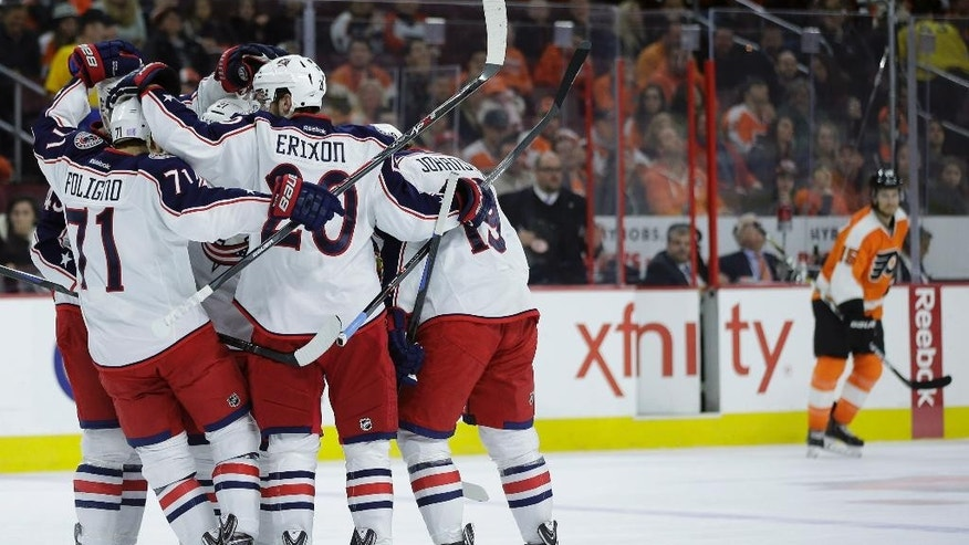 Columbus Blue Jackets Nick Foligno (71), Time Erixon(20) and Ruan  Johansen (19)  celebrate  with  team maters after a goal by James Wisniewski during the first period of an NHL hockey game against the Philadelphia Flyers, Friday, Nov. 14, 2014, in Philadelphia. (AP Photo/Matt Slocum)