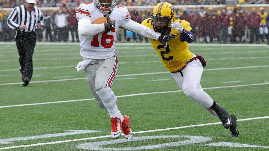 Ohio State quarterback J.T. Barrett (16) fends off Minnesota defensive back Cedric Thompson (2) as he runs for a gain during the second quarter of an NCAA college football game in Minneapolis Saturday, Nov. 15, 2014. Ohio State won 31-24. (AP Photo/Ann Heisenfelt)