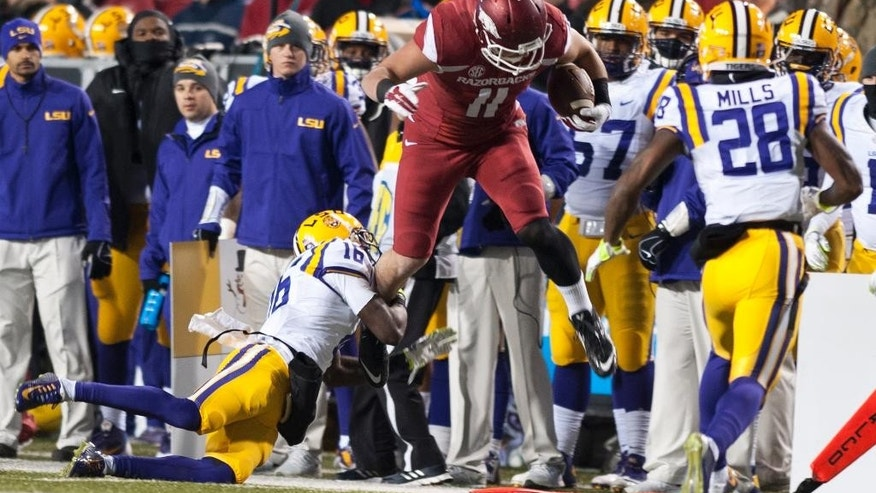 Arkansas' A.J. Derby (11) leaps past LSU's Tre'Davious White (16) during the first half of an NCAA college football game in Fayetteville, Ark., Saturday, Nov. 15, 2014. (AP Photo/Sarah Bentham)