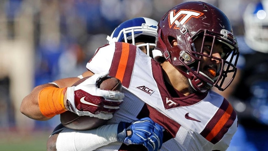 Virginia Tech's Bucky Hodges (7) runs the ball as Duke's Breon Borders tackles him from behind during the first half of an NCAA college football game in Durham, N.C., Saturday, Nov. 15, 2014. (AP Photo/Gerry Broome)