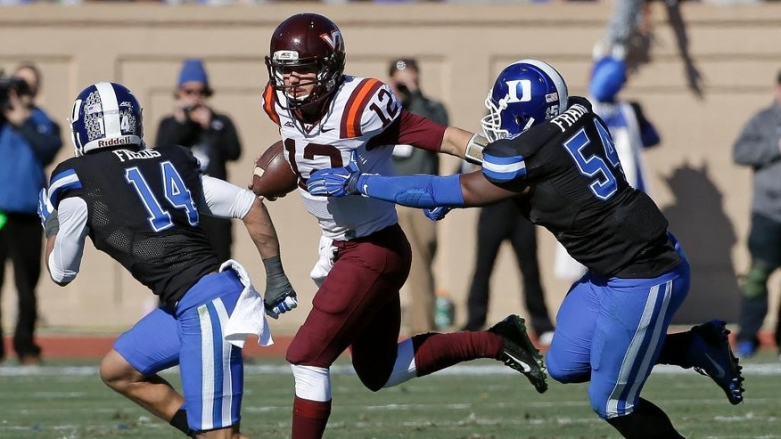 Duke's Bryon Fields (14) and C.J. France (54) chase Virginia Tech quarterback Michael Brewer (12) during the first half of an NCAA college football game in Durham, N.C., Saturday, Nov. 15, 2014. (AP Photo/Gerry Broome)