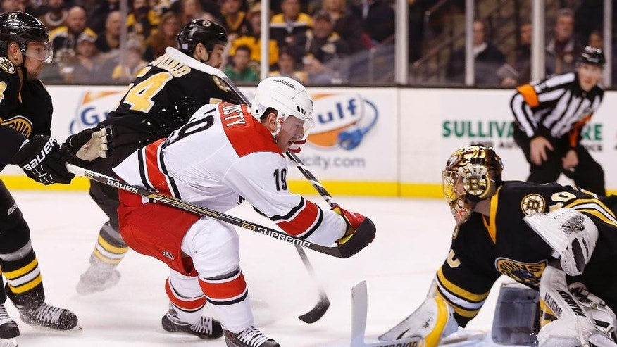 Carolina Hurricanes' Jiri Tlusty (19), of the Czech Republic, can not get the shot off against Boston Bruins goalie Tuukka Rask, of Finland, right, after a hooking penalty by Bruins' Adam McQuaid (54) during the first period of an NHL hockey game in Boston, Saturday, Nov. 15, 2014. (AP Photo/Michael Dwyer)