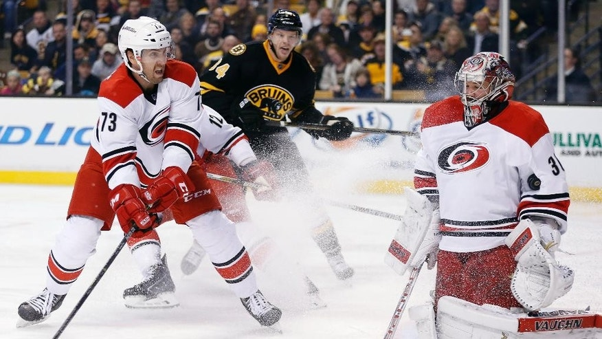 Carolina Hurricanes' Brett Bellemore (73) watches as Cam Ward (30) stops a shot by the Boston Bruins during the second period of an NHL hockey game in Boston, Saturday, Nov. 15, 2014. (AP Photo/Michael Dwyer)