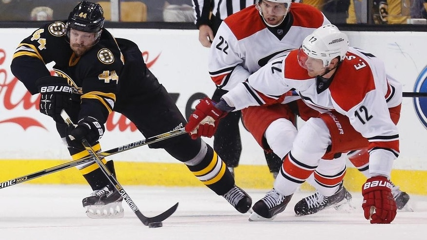 Boston Bruins' Dennis Seidenberg (44), of Germany, battles Carolina Hurricanes' Zach Boychuk (22) and Eric Staal (12) for the puck during the second period of an NHL hockey game in Boston, Saturday, Nov. 15, 2014. (AP Photo/Michael Dwyer)