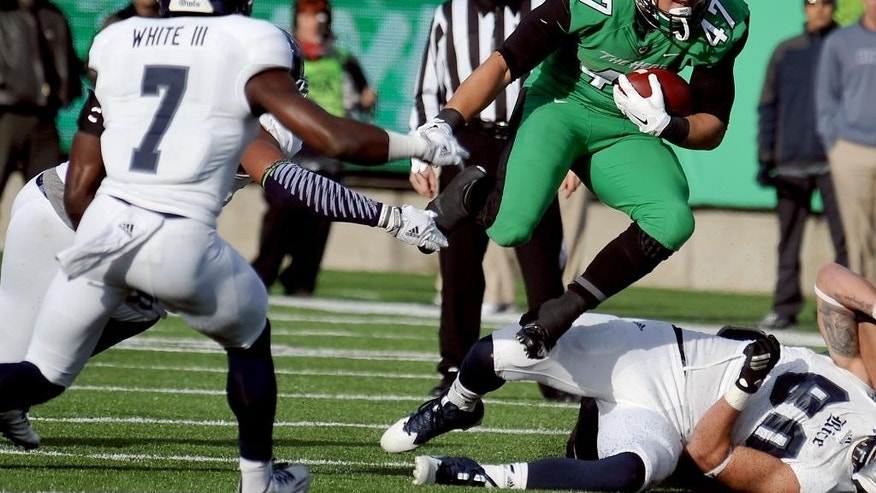 Marshall's Devon Johnson (47) leaps over a Rice defender during an NCAA football game in Huntington, W.Va., Saturday, Nov. 15, 2014. (AP Photo/Chris Tilley)