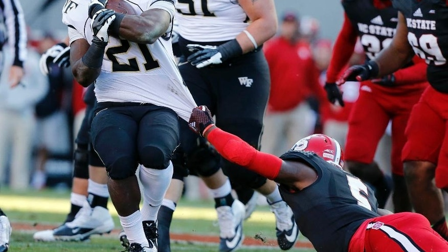 Wake Forest running back Isaiah Robinson (21) is tackled by N.C. State linebacker Rodman Noel (5) during the first half of an NCAA college football game against Wake Forest in Raleigh, N.C., Saturday, Nov. 15, 2014. (AP Photo/The News & Observer, Ethan Hyman)