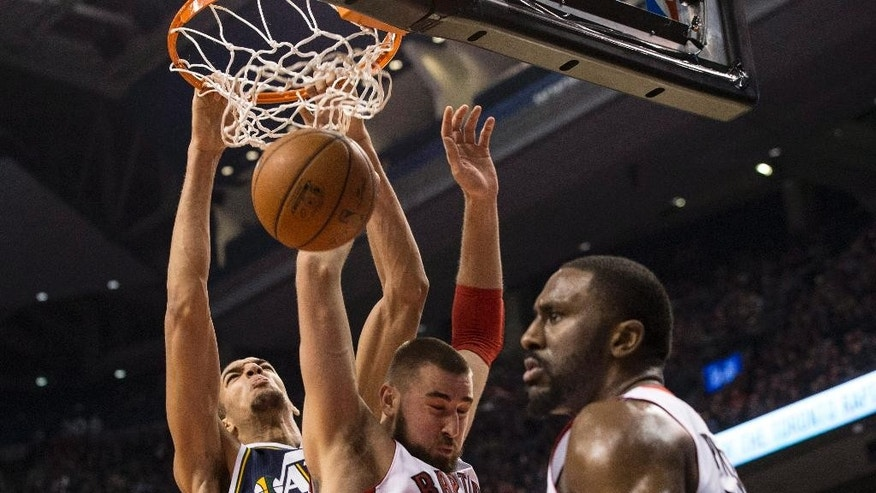 Utah Jazz's Rudy Gobert, left, and Toronto Raptors' Jonas Valanciunas, center, battle for the ball under the hoop as Raptors' Patrick Patterson looks on during first-half NBA basketball game action in Toronto, Saturday, Nov. 15, 2014. (AP Photo/The Canadian Press, Chris Young)