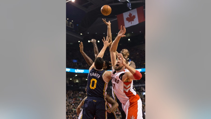 Toronto Raptors' Jonas Valanciunas, right, is out-muscled on a offensive rebound by the Utah Jazz defense during first-half NBA basketball game action in Toronto, Saturday, Nov. 15, 2014. (AP Photo/The Canadian Press, Chris Young)
