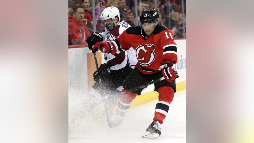 The puck flies up in the air as New Jersey Devils right wing Stephen Gionta (11) and Colorado Avalanche defenseman Jan Hejda, of the Czech Republic, challenge each other during the second period of an NHL hockey game, Saturday, Nov. 15, 2014, in Newark, N.J. (AP Photo/Julio Cortez)
