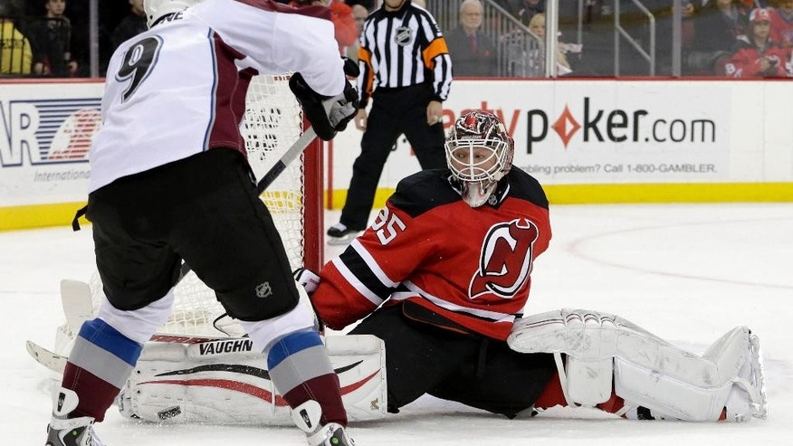 New Jersey Devils goalie Cory Schneider blocks a shot by Colorado Avalanche center Matt Duchene during the first period of an NHL hockey game, Saturday, Nov. 15, 2014, in Newark, N.J. (AP Photo/Julio Cortez)