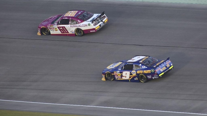 Chase Elliott (9) tries to get around Chris Buescher (60) during the NASCAR Nationwide series auto race Saturday, Nov. 15, 2014 in Homestead, Fla. (AP Photo/Jim Topper)