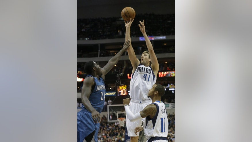 Dallas Mavericks forward Dirk Nowitzki (41) of Germany shoots over Minnesota Timberwolves forward Anthony Bennett (24) as Monta Ellis (11) looks on during the first half of an NBA basketball game, Saturday, Nov. 15, 2014, in Dallas. (AP Photo/LM Otero)