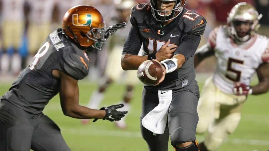 Miami quarterback Brad Kaaya, right, hands off to running back Duke Johnson (8) during the first half of an NCAA college football game against Florida State, Saturday, Nov. 15, 2014, in Miami Gardens, Fla. (AP Photo/Wilfredo Lee)