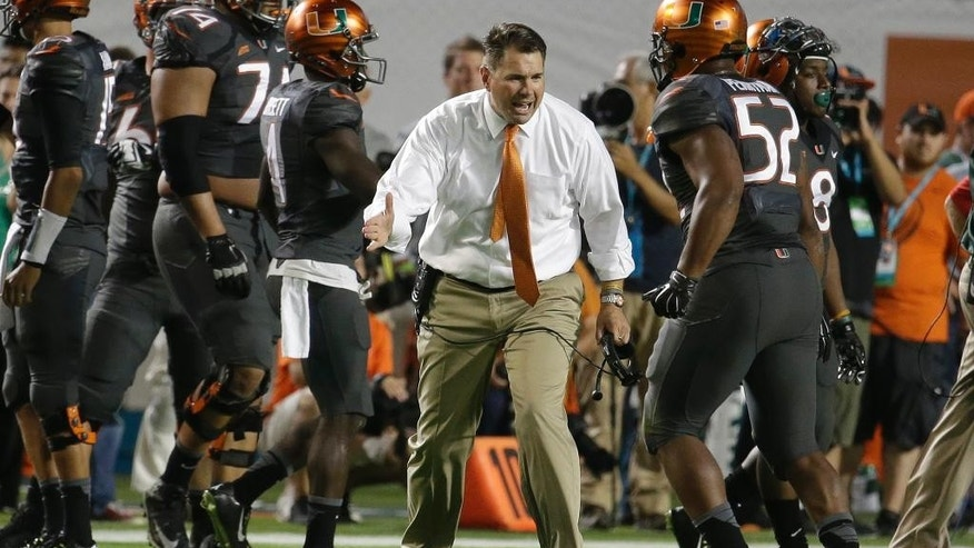 Miami head coach Al Golden, center, greets linebacker Denzel Perryman (52) in the first half an NCAA college football game against Florida State, Saturday, Nov. 15, 2014, in Miami Gardens, Fla. (AP Photo/Lynne Sladky)