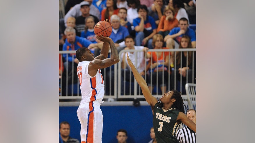 Florida forward Dorian Finney-Smith (10) shoots for three points with William & Mary guard Marcus Thornton (3) trying to block the shot during the second half of NCAA College basketball  in Gainesville, Fla., Friday, Nov., 14, 2014. Florida defeated William & Mary 68-45. (AP Photo/Phil Sandlin)