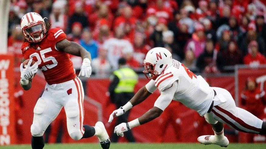 Wisconsin's Melvin Gordon gets away from Nebraska's Randy Gregory during the first half of an NCAA college football game Saturday, Nov. 15, 2014, in Madison, Wis. (AP Photo/Morry Gash)