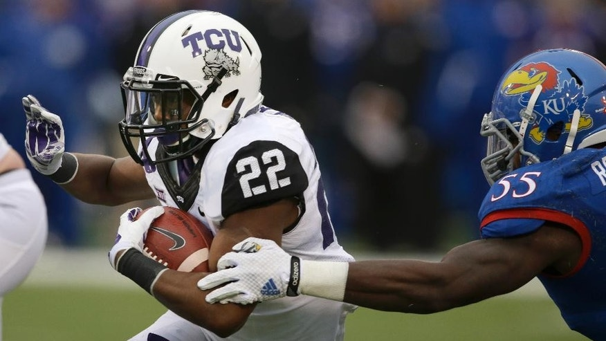 TCU running back Aaron Green (22) gets away from Kansas linebacker Michael Reynolds (55) during the first half of an NCAA college football game in Lawrence, Kan., Saturday, Nov. 15, 2014. (AP Photo/Orlin Wagner)