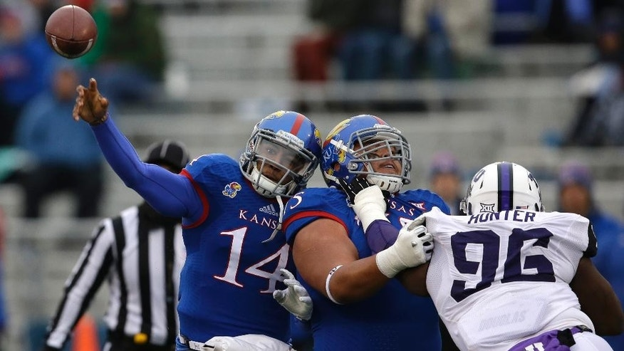 Kansas offensive lineman Junior Visinia (75) blocks TCU defensive tackle Chucky Hunter (96) in front of Kansas quarterback Michael Cummings (14) during the first half of an NCAA college football game in Lawrence, Kan., Saturday, Nov. 15, 2014. (AP Photo/Orlin Wagner)