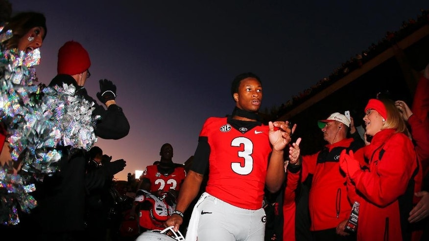 Georgia running back Todd Gurley (3) walks through a crowd of fans as he arrives at Sanford Stadium for an NCAA college football game against Auburn Saturday, Nov. 15, 2014, in Athens, Ga. (AP Photo/John Bazemore)