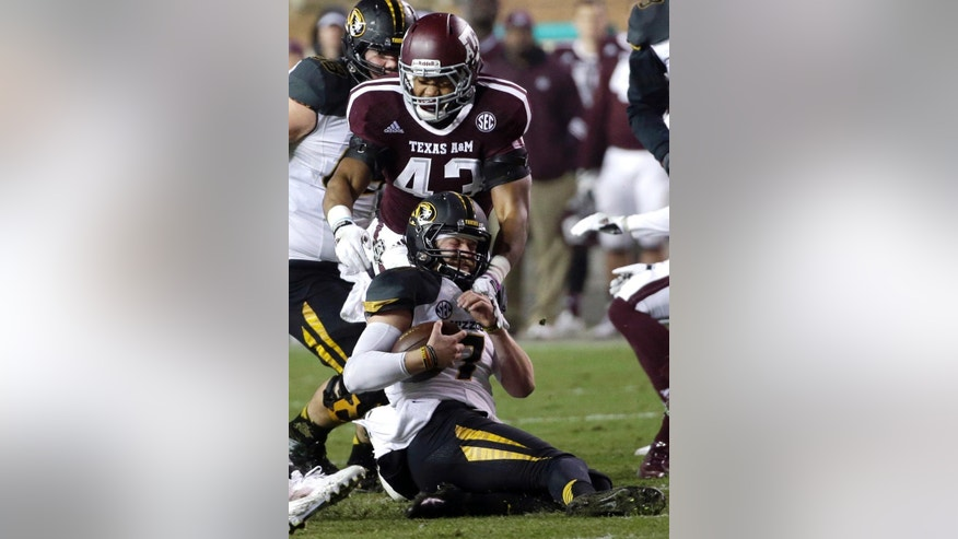 Missouri quarterback Maty Mauk (7) slides before being hit by Texas A&M linebacker Justin Bass (43) during the second quarter of an NCAA college football game Saturday, Nov. 15, 2014, in College Station, Texas. (AP Photo/David J. Phillip)