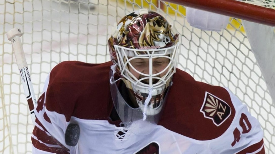 Arizona Coyotes goalie Devan Dubnyk stops a shot by Vancouver Canucks' Chris Higgins during the second period of an NHL hockey game in Vancouver,British Columbia, on Friday Nov. 14, 2014. (AP Photo/The Canadian Press, Darryl Dyck)