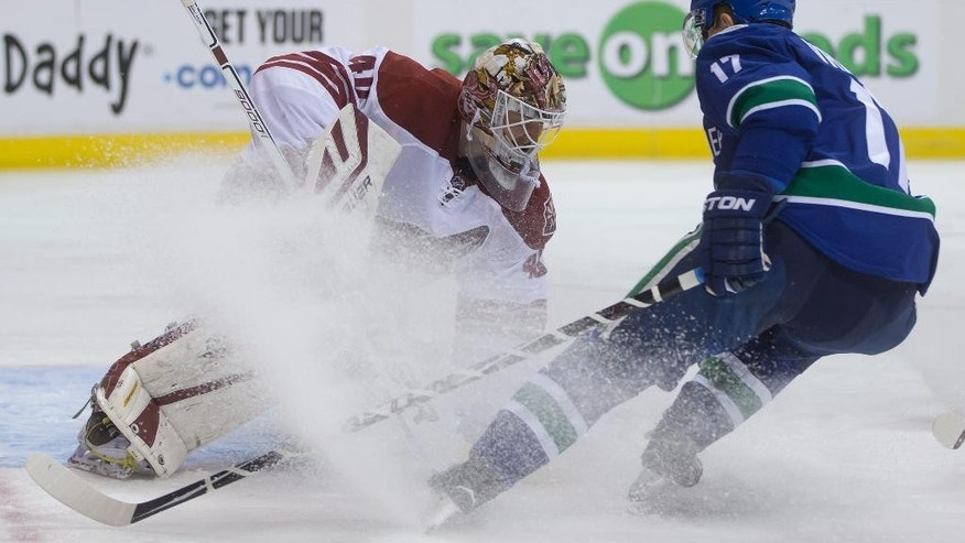 Arizona Coyotes goalie Devan Dubnyk, left, covers up the puck as Vancouver Canucks' Radim Vrbata, of the Czech Republic, skates in during the first period of an NHL hockey game in Vancouver,  British Columbia, on Friday Nov. 14, 2014.(AP Photo/The Canadian Press, Darryl Dyck)