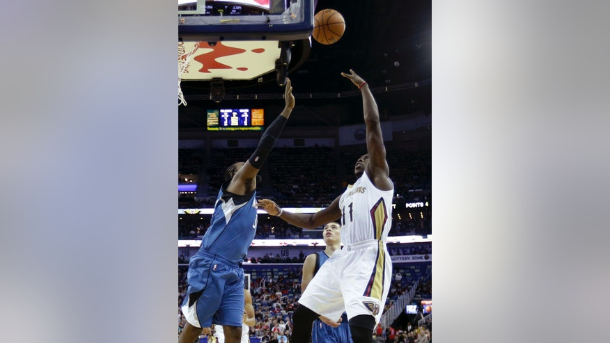 New Orleans Pelicans guard Jrue Holiday (11) shoots over Minnesota Timberwolves center Ronny Turiaf (32) in the second half of an NBA basketball game in New Orleans, Friday, Nov. 14, 2014. The Pelicans won 139-91. (AP Photo/Gerald Herbert)
