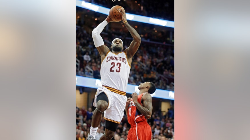 Cleveland Cavaliers' LeBron James (23) goes in for a dunk on Atlanta Hawks' Jeff Teague in the first quarter of an NBA basketball game Saturday, Nov. 15, 2014, in Cleveland. (AP Photo/Mark Duncan)