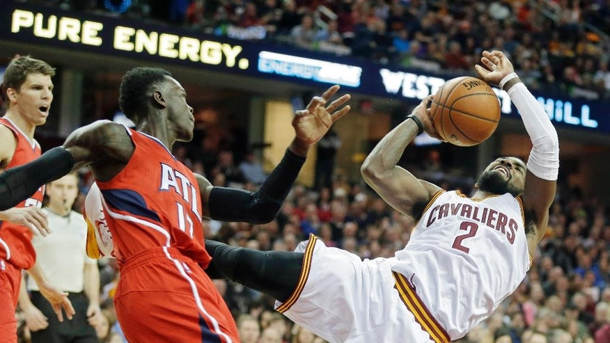 Cleveland Cavaliers' Kyrie Irving (2) is fouled by Atlanta Hawks' Dennis Schroder, from Germany, in the first quarter of an NBA basketball game Saturday, Nov. 15, 2014, in Cleveland. (AP Photo/Mark Duncan)