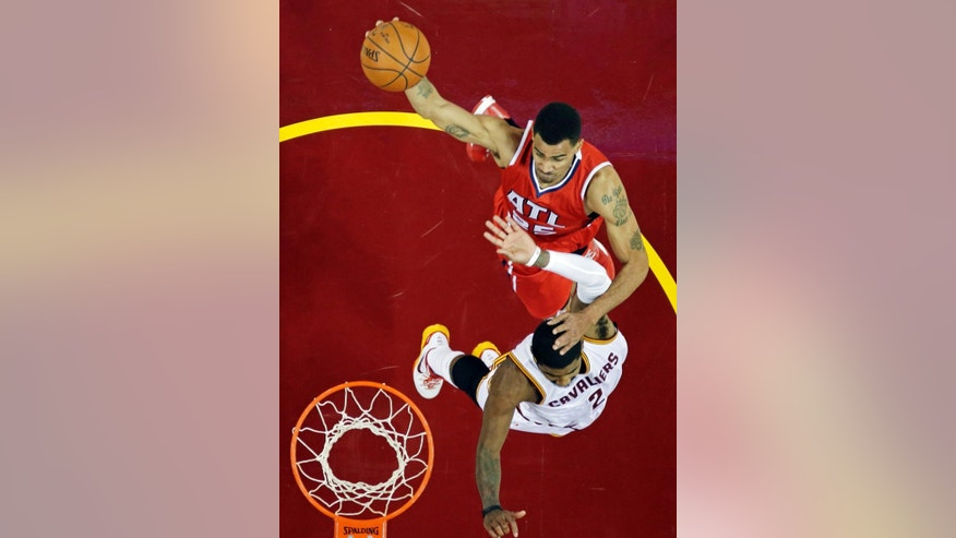 Atlanta Hawks' Thabo Sefolosha, from Switzerland, top, goes over Cleveland Cavaliers' Kyrie Irving for a shot in the first half of an NBA basketball game Saturday, Nov. 15, 2014, in Cleveland. (AP Photo/Mark Duncan)