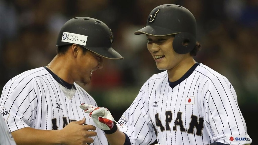 Japan's shortstop Hayato Sakamoto, right, is celebrated by teammate Sho Nakata after hitting a two-run home run off MLB All-Stars starter Jeremy Guthrie in the second inning of Game 3 of their exhibition baseball series at Tokyo Dome in Tokyo, Saturday, Nov. 15, 2014. (AP Photo/Koji Sasahara)