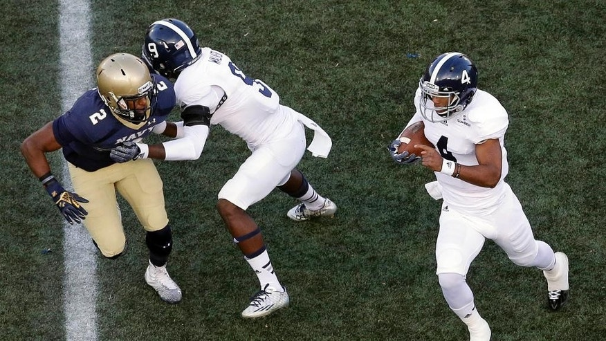 Georgia Southern quarterback Kevin Ellison, right, rushes the ball as teammate Zach Walker blocks Navy safety Parrish Gaines, left, in the first half of an NCAA college football game, Saturday, Nov. 15, 2014, in Annapolis, Md. (AP Photo/Patrick Semansky)