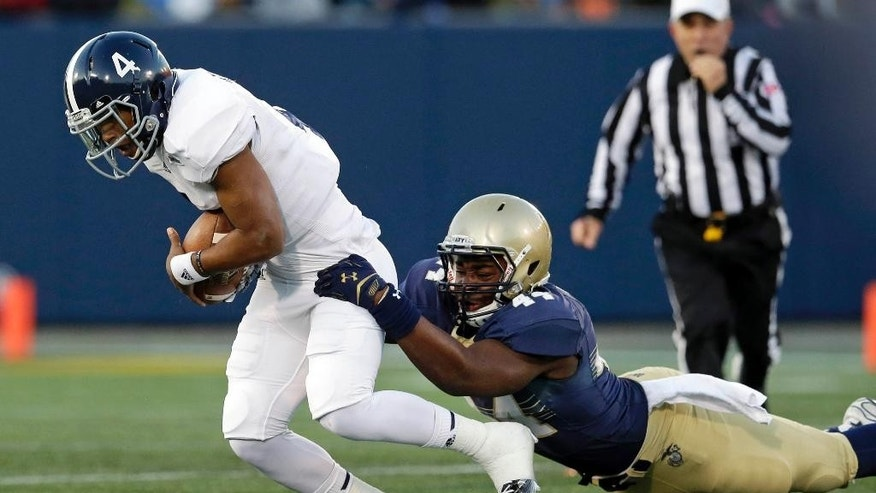 Georgia Southern quarterback Kevin Ellison, left, is tackled by Navy linebacker Obi Uzoma in the first half of an NCAA college football game, Saturday, Nov. 15, 2014, in Annapolis, Md. (AP Photo/Patrick Semansky)