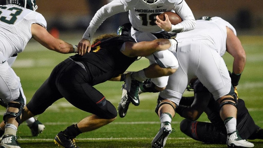 Michigan State quarterback Connor Cook (18) runs with the ball against Maryland linebacker Cole Farrand, left, during the first half of an NCAA college football game, Saturday, Nov. 15, 2014, in College Park, Md. (AP Photo/Nick Wass)