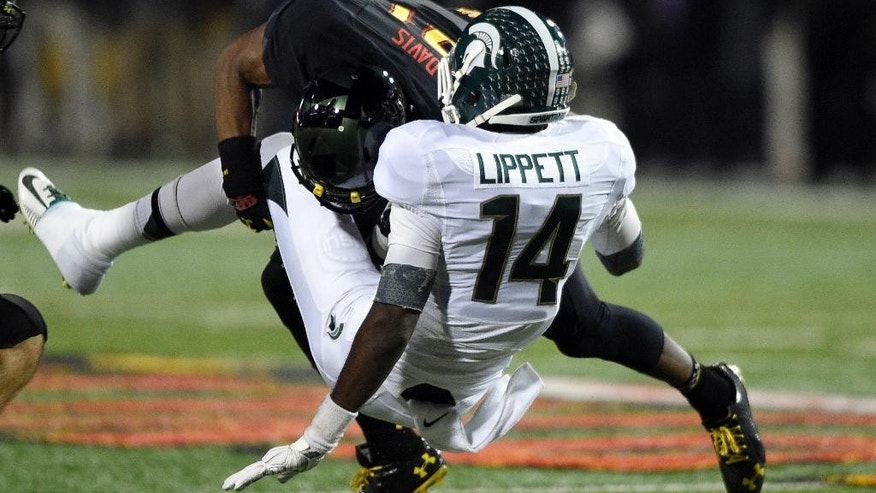 Maryland defensive back Sean Davis (21) tackles Michigan State wide receiver Tony Lippett (14) during the first half of an NCAA college football game, Saturday, Nov. 15, 2014, in College Park, Md. (AP Photo/Nick Wass)
