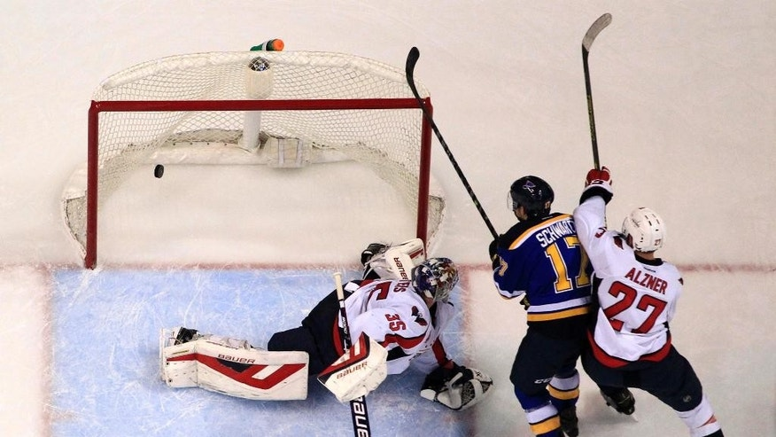 St. Louis Blues' Jaden Schwartz, center, scores past Washington Capitals goalie Justin Peters, left, and Karl Alzner, right, during the second period of an NHL hockey game Saturday, Nov. 15, 2014, in St. Louis. (AP Photo/Jeff Roberson)